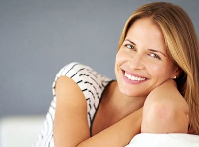 Head-and-shoulders photo of a strawberry-blonde woman sitting on a white couch and smiling, for information on Hoffman Estates emergency dentistry from William Becker, DDS.