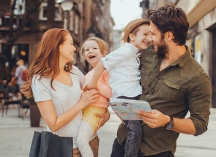 Photo of parents, their son, and their daughter outdoors with a downtown city-like scene in the background, for family dentistry from Dr. William Becker of Hoffman Estates.