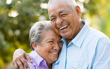 Head-and-shoulders photo of elderly couple hugging and smiling for information on affordable dentistry, from Poplar Crossing Dental in Hoffman Estates.