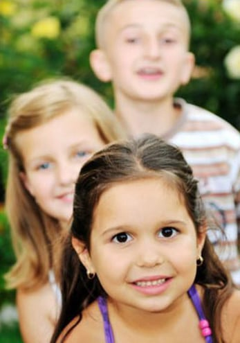 Photo of three children - one standing behind another. In front is a brunette girl with brown eyes, about four years old. Behind her is a blonde girl with long hair and blue eyes, about 7 years old, and behind her is a blonde boy with dark eyes, about 12 year old, for information on dental tips for parents from Hoffman Estates Dr. Becker.