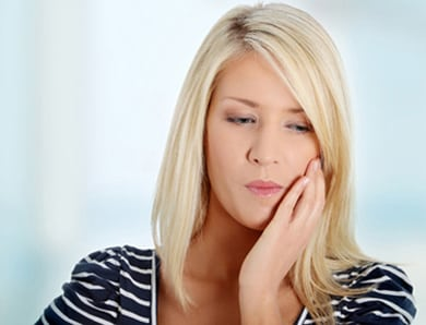 Head-and-shoulders photo of a blonde woman holding the left side of her face with her left hand; for information on toothaches from Dr. Becker of Hoffman Estates.