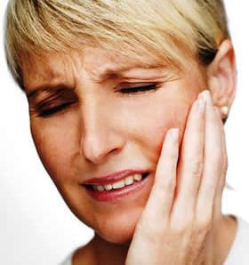 A woman grabbing her jaw in pain from TMJ