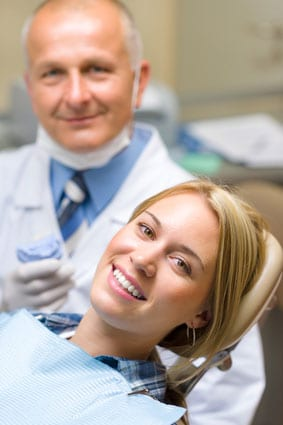 Woman smiling in dental chair with her dentist beside her