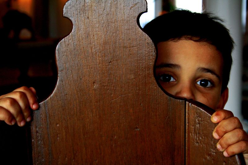 boy cowering behind chair
